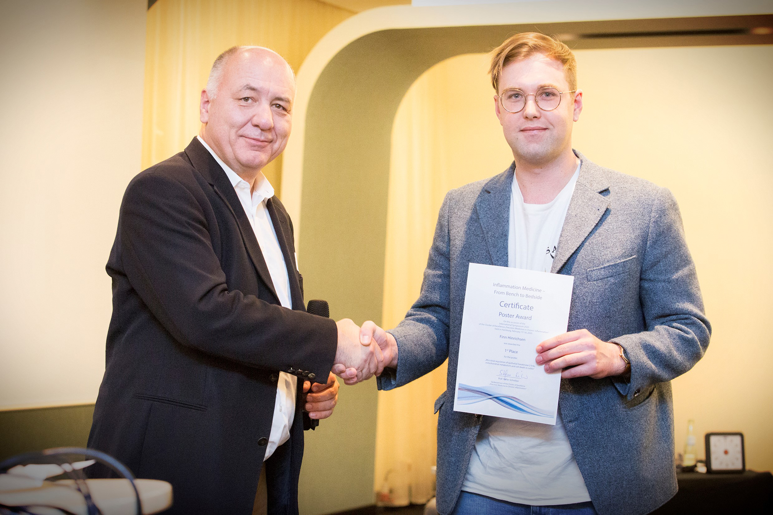 Poster price for Finn Hinrichsen awarded by Prof. Dr. Stefan Schreiber,  photos: C. Kloodt, copyright: Cluster of Excellence PMI, Kiel University